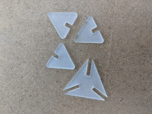 laser cutted four pieces of white triangles with slots inside of them
