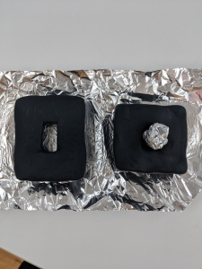 shapes of two cubes with middle part carved out using baked black clay